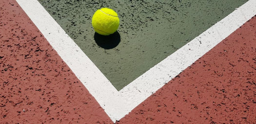High angle view of yellow tennis ball on court