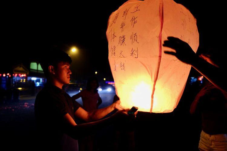 People holding illuminated lantern at night