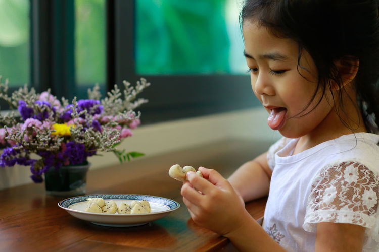Close-up of smiling girl with ice cream in plate on table