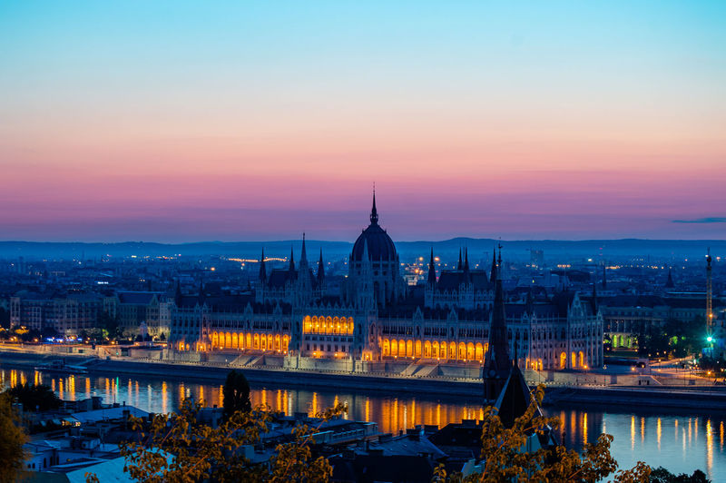 Hungarian parliament building by danube river against sky at dusk