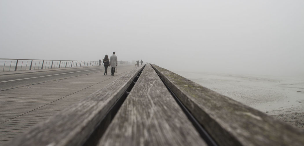 Walking Fog Full Length The Way Forward Outdoors Adult Day Adventure One Man Only People Cold Temperature Adults Only One Person Beauty In Nature Only Men Nature Sky Outdoor Pursuit Low Angle View Beach Day Tranquility Built Structure Mont Sant Michel City Ancient