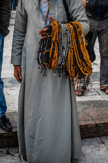 Low Section Of Man Selling Religious Beads Necklace While Standing In Market