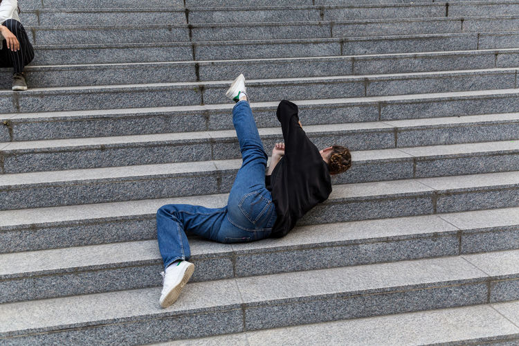 Dancer lying on outdoor staircase steps One Person Casual Clothing Jeans Staircase Caucasian Young Woman Young Adult Outdoors Outside Natural Lighting Steps And Staircases Full Length Real People Dancing Lying On Floor Female Unrecognizable Person Day Youth Culture