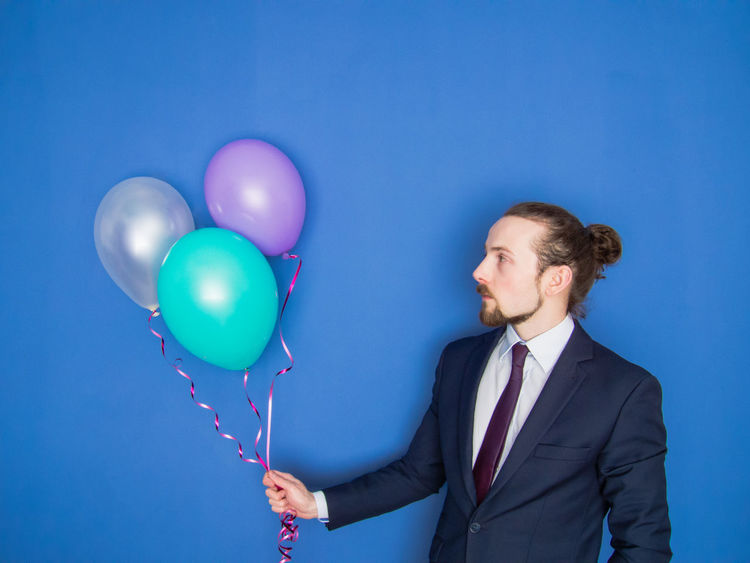 Young handsome bearded man in a suit holding group of colorful balloons and looking at them. Blue background. Balloon Beard Blowing Up Balloon Blue Business Business Finance And Industry Businessman Carefree Confidence  Economy Elegant Flower Helium Balloon Holding Man Manager One Person Party Person Relax Self Portrait Suit Well-dressed Young Adult