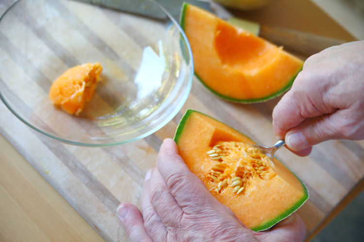 Scooping seeds from fresh cantaloupe Healthy Eating Food One Person Unrecognizable Person Orange Color Close-up Melon Fresh Fruit Cutting Board Glass Bowl Overhead Natural Light Wood Surface Textures Studio Shot Indoors  Point Of View Holding Removing Seeds Food Prep