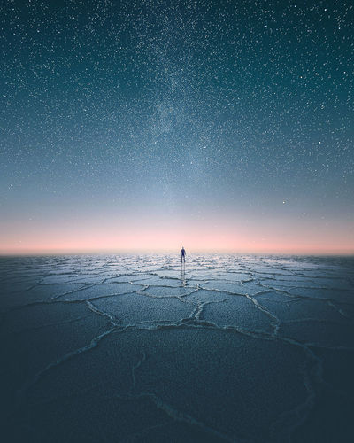 Distant Man Standing On Scenic Salt Flat Against Starry Sky At Night