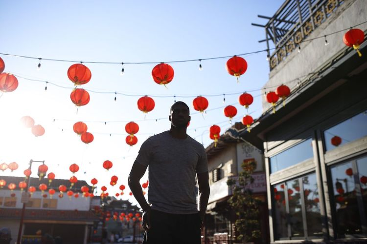 Low angle view of young man standing against lanterns in city