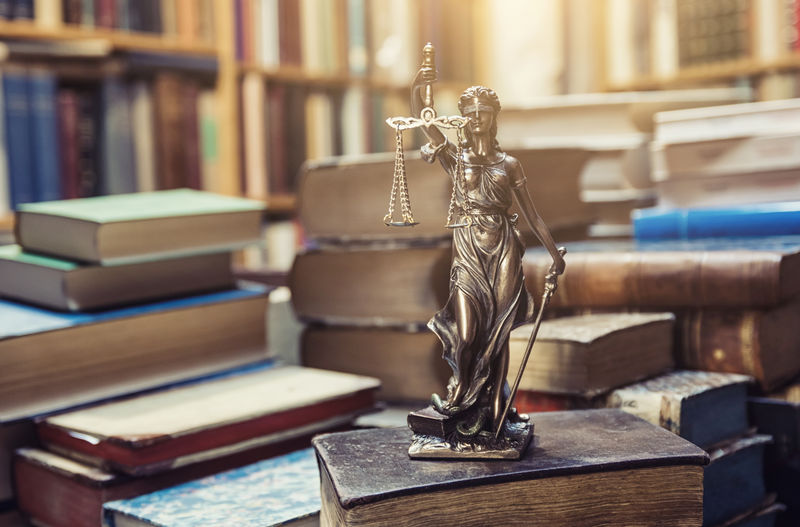 Close-up of lady justice statue on book