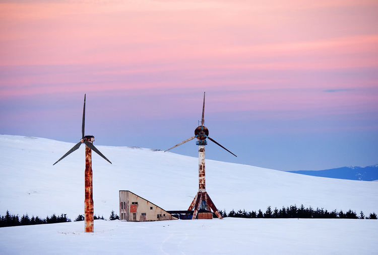 Windmills on snow covered landscape against sky during sunset