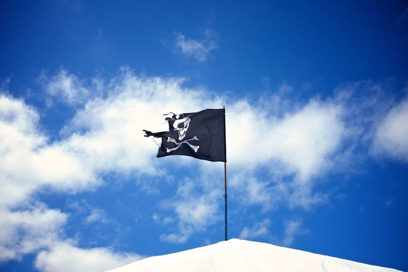 Low angle view of torn pirate flag against sky