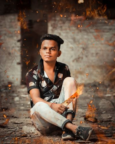 Digital composite image of young man sitting amidst fire