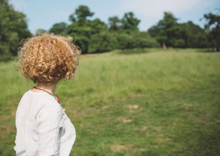 Side View Of Woman Standing On Grassy Field