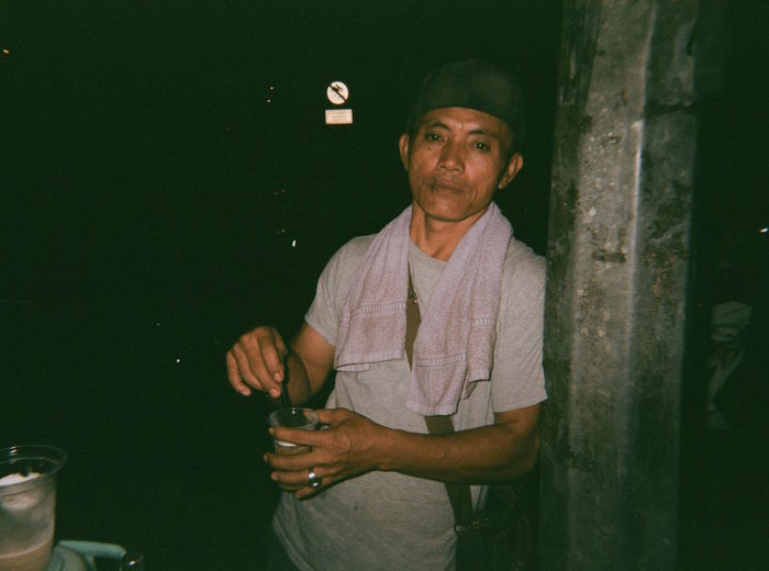 Portrait Of Mid Adult Man With Drink Standing By Pole At Night