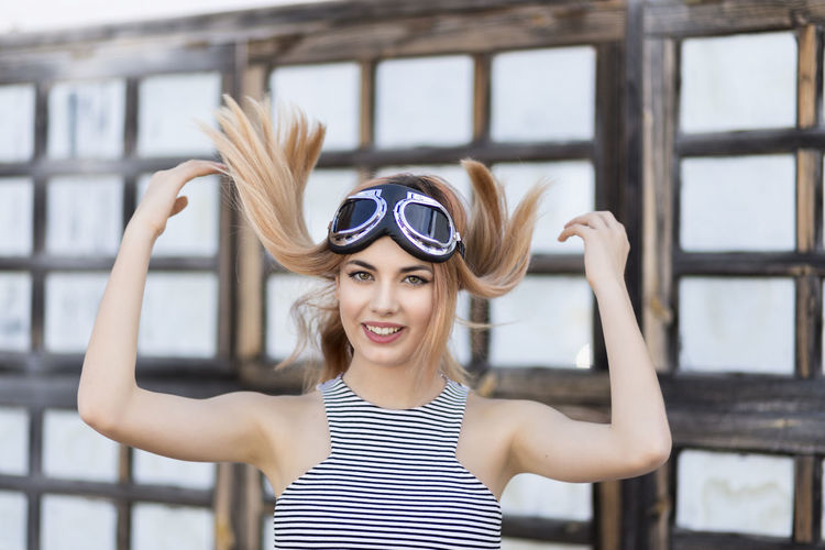 Portrait of smiling young woman with long blond hair wearing flying goggles