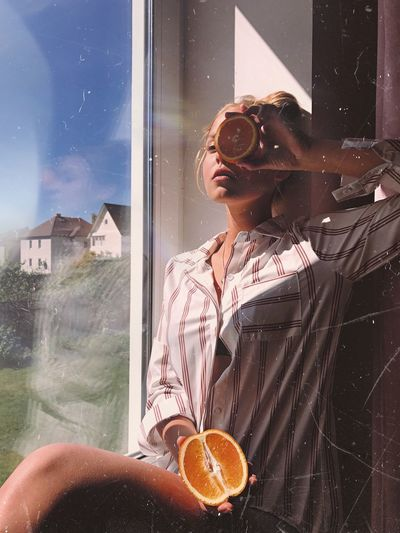 Young woman with halved citrus fruit sitting by window at home