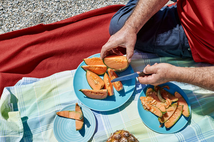 Middle aged couple having a picnic at the seaside with fresh exotic fruit. man cuts a melon.