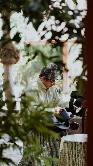 Mature man reading book seen through plants