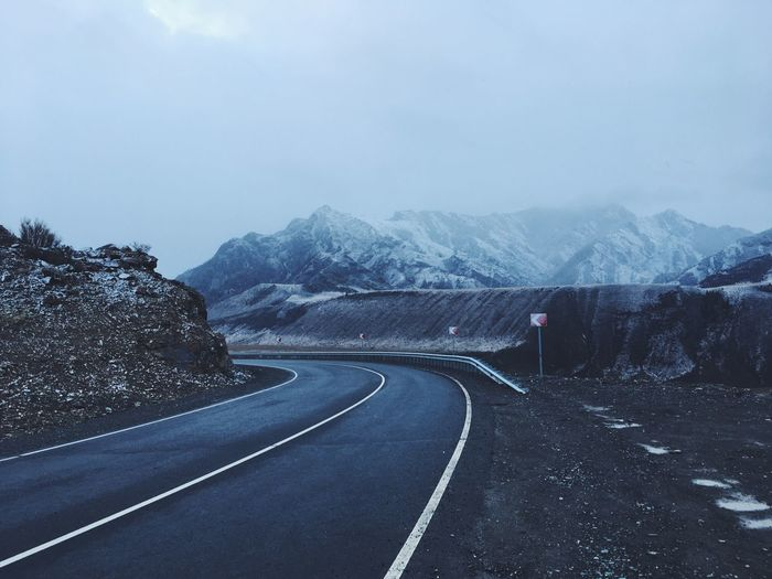 Empty road along mountain range against sky. altai