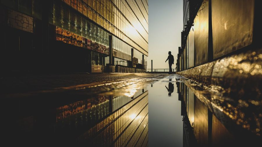 Silhouette man amidst buildings reflecting on puddle in city during sunset