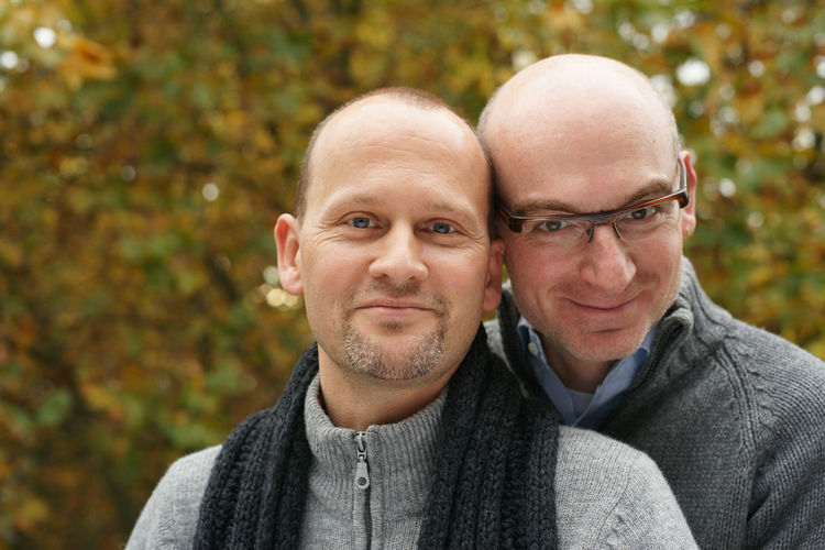 Portrait Of Smiling Gay Couple Against Trees In Park