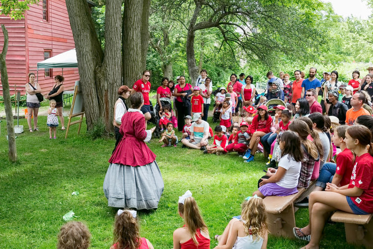 NORTH YORK, CANADA - JULY 01, 2017: A street play about Canada at the Black Creek Pioneer Village on the Dramatic Sky Adult Crowd Day Drink Festival Field Grass Group Of People Large Group Of People Leisure Activity Lifestyles Men Nature Outdoors Park Plant Play Playing Real People Sitting Spectator Togetherness Tree Women