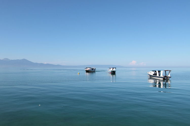 Scenic view of empty motorboats and sulawesi sea against clear sky