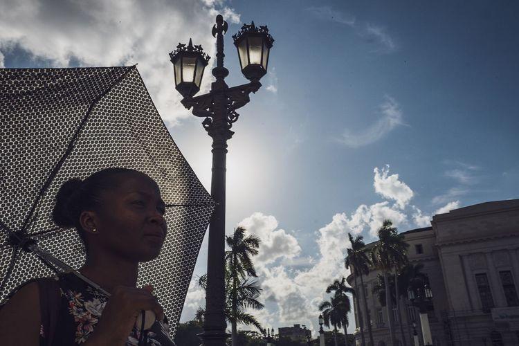 Low angle portrait of woman against building against sky