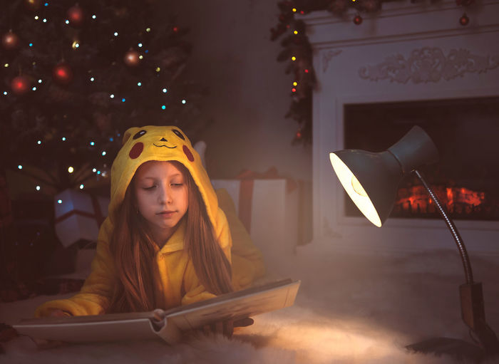 Portrait of young woman in illuminated christmas tree at home