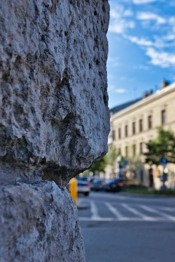 Close-up of rock by building in city against sky
