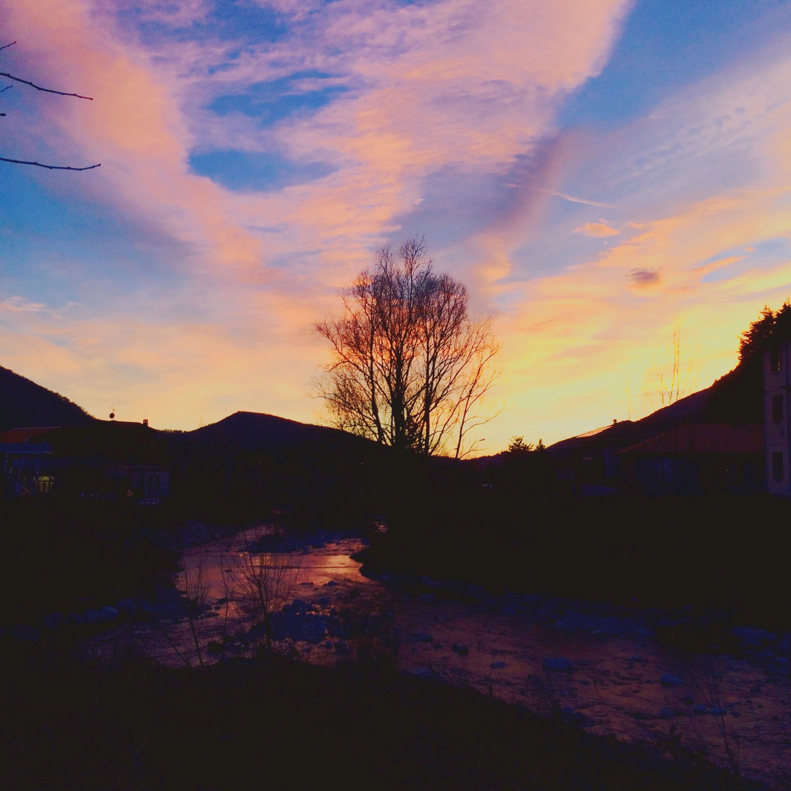 sunset, silhouette, sky, tranquil scene, scenics, tree, tranquility, beauty in nature, orange color, cloud - sky, water, nature, bare tree, built structure, idyllic, mountain, cloud, river, architecture, dusk