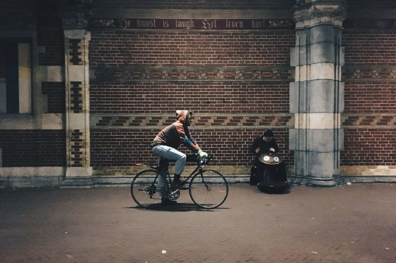 Full length of man cycling on bicycle in city