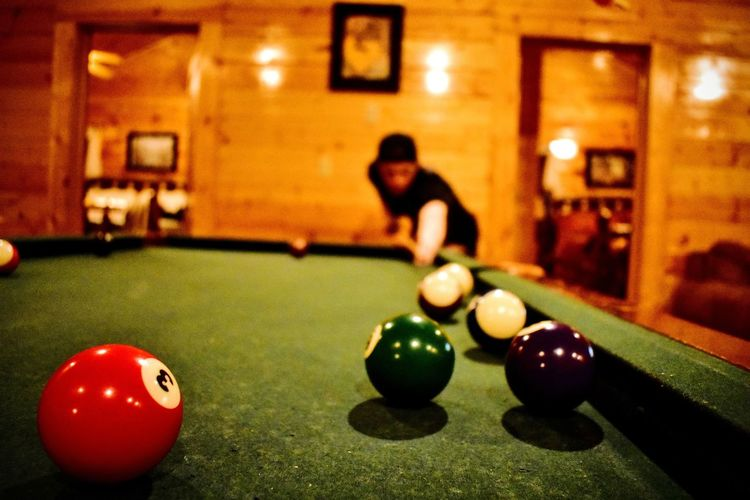 Billards  Pool Balls Pool Stick Lodge House Cabin In The Mountains Indoors  Playing Real People Only Men Young Adult Males  Adult Activity Sport People Adults Only Close-up Action Shot  Shallow Depth Of Field One Person Indoors  Illuminated Motion Blurry Background Blurryface Investing In Quality Of Life