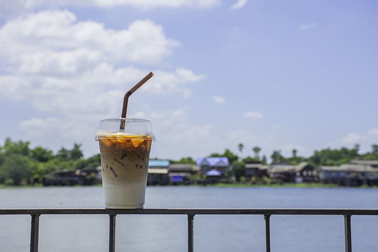 Glass of cold espresso coffee on the iron balcony Background views of the river and the home. Tropical Green Healthy Food Juice Cold Background Glass Aroma Beautiful Beverage Black Breakfast Brown Cafe Caffeine Cappuccino Chocolate City Cocktail Coffee Cool Drink Dwelling Espresso Fresh Ice Landscape Latte Lifestyle Milk Mocha Modern Natural Nature Orange Outdoor Panorama Plastic Refreshment Relax Residential  River Sky Straw Sugar Summer Sweet Tasty Water
