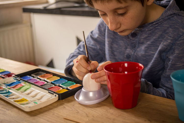 Boy painting eggshell at table
