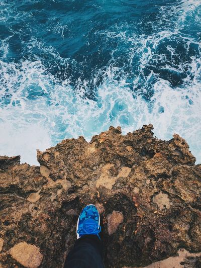 Low Section Of Person On Rock Over Sea