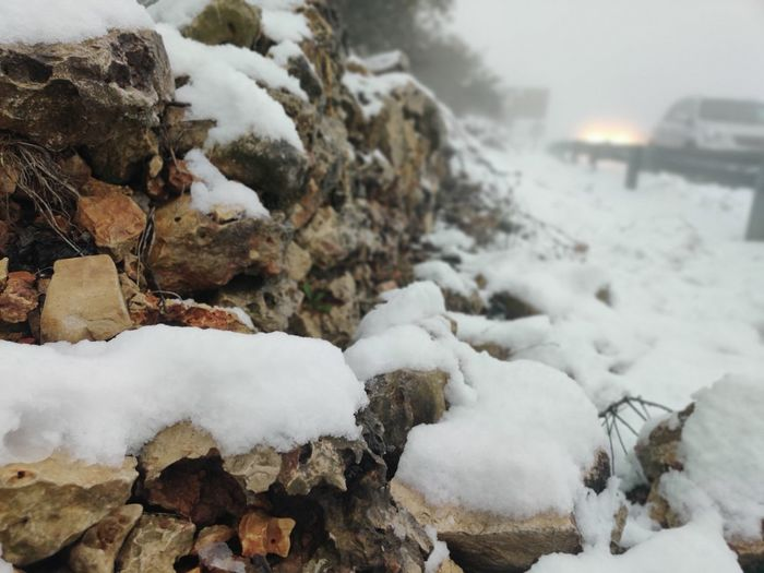 Close-up of snow covered rocks on field