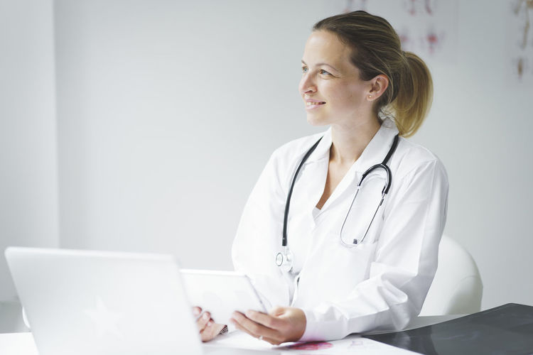 Smiling doctor looking away while holding digital tablet at clinic