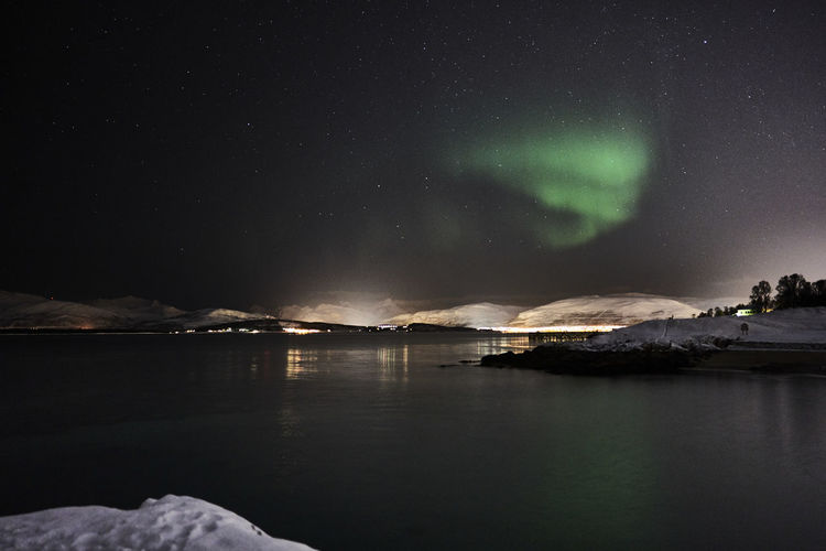 Scenic view of lake against sky at night in tromso with aurora borealis