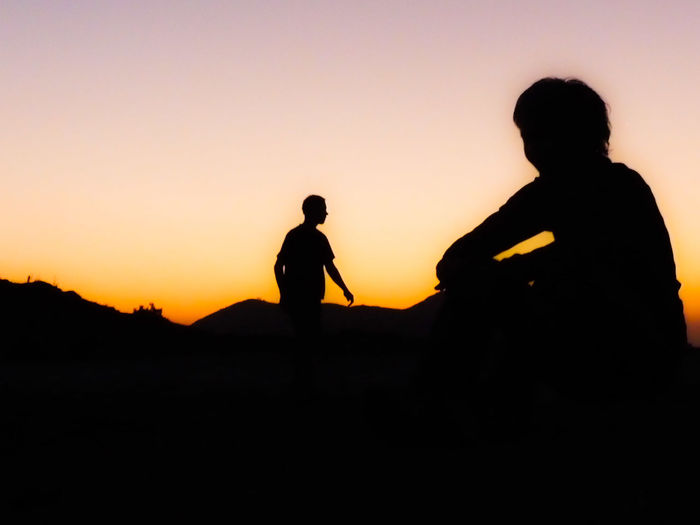 Silhouette children playing against sky during sunset