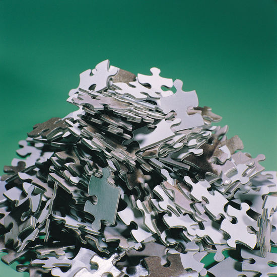 Close-up of puzzle piece against colored background