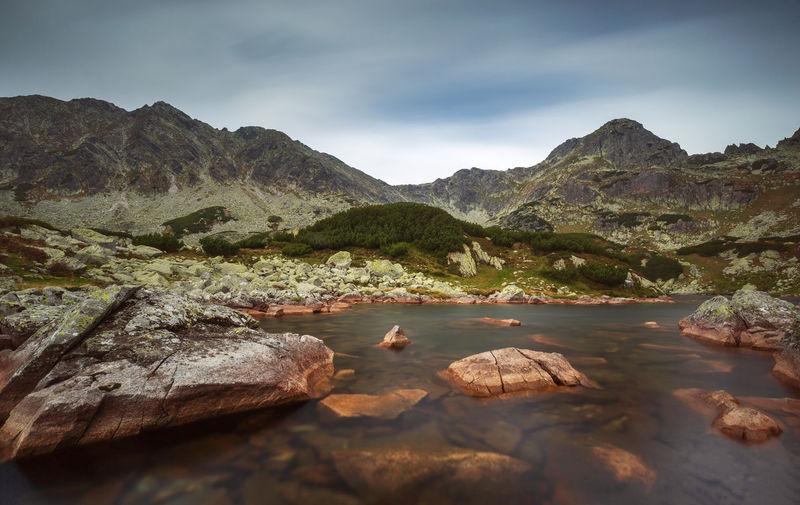 Rocks on shore by lake against sky in retezat mountains