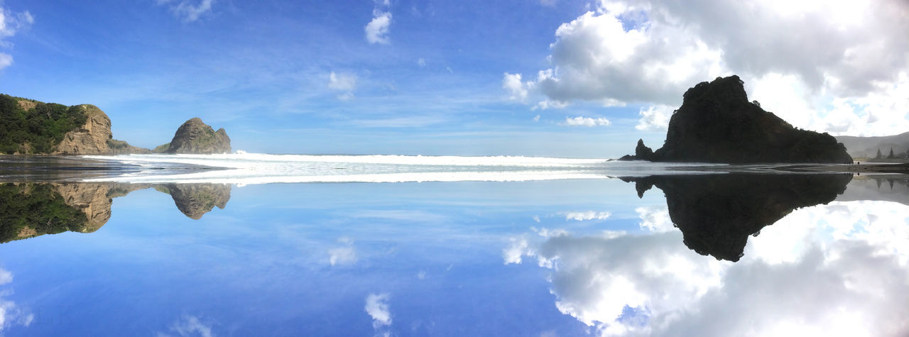 Reflection Of Lion Rock At Piha Beach Against Sky