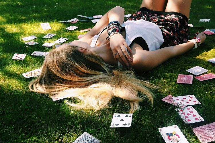 Woman Lying On Grass Surrounded With Cards