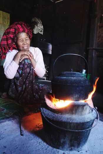 Inside a bamboo hut: old lady cooking water for green tea Women Burma Burmese Myanmar Boiling One Person Childhood Real People Fire Burning Front View Child Lifestyles Heat - Temperature Females