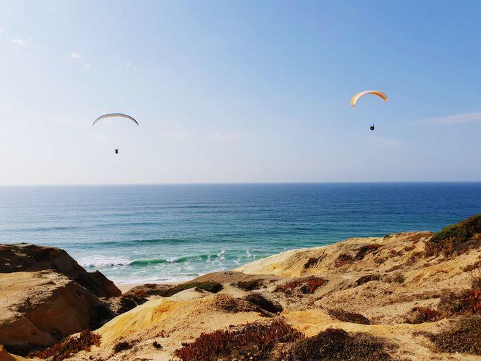 Sea and wind Paragliding Water Parachute Flying Extreme Sports Sea Wave Beach Sport Sunset Surf Coastline Shore Sandy Beach Horizon Over Water Ocean Seascape Rocky Coastline