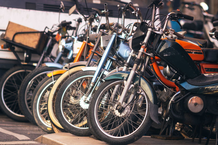 Close-up of vintage bicycles, mopeds and solex in parking lot