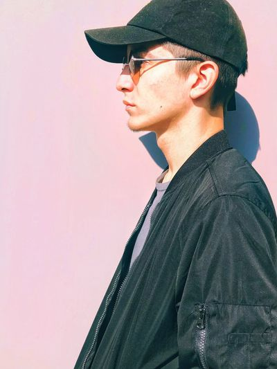 Portrait of young man looking away while standing against wall
