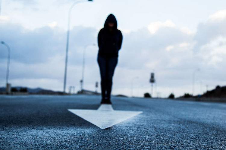 Man Standing On Arrow Marking Over Road Against Sky