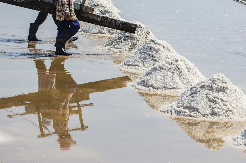 Reflection of salt farmers on a water surface in a salt field at phetchaburi, thailand.