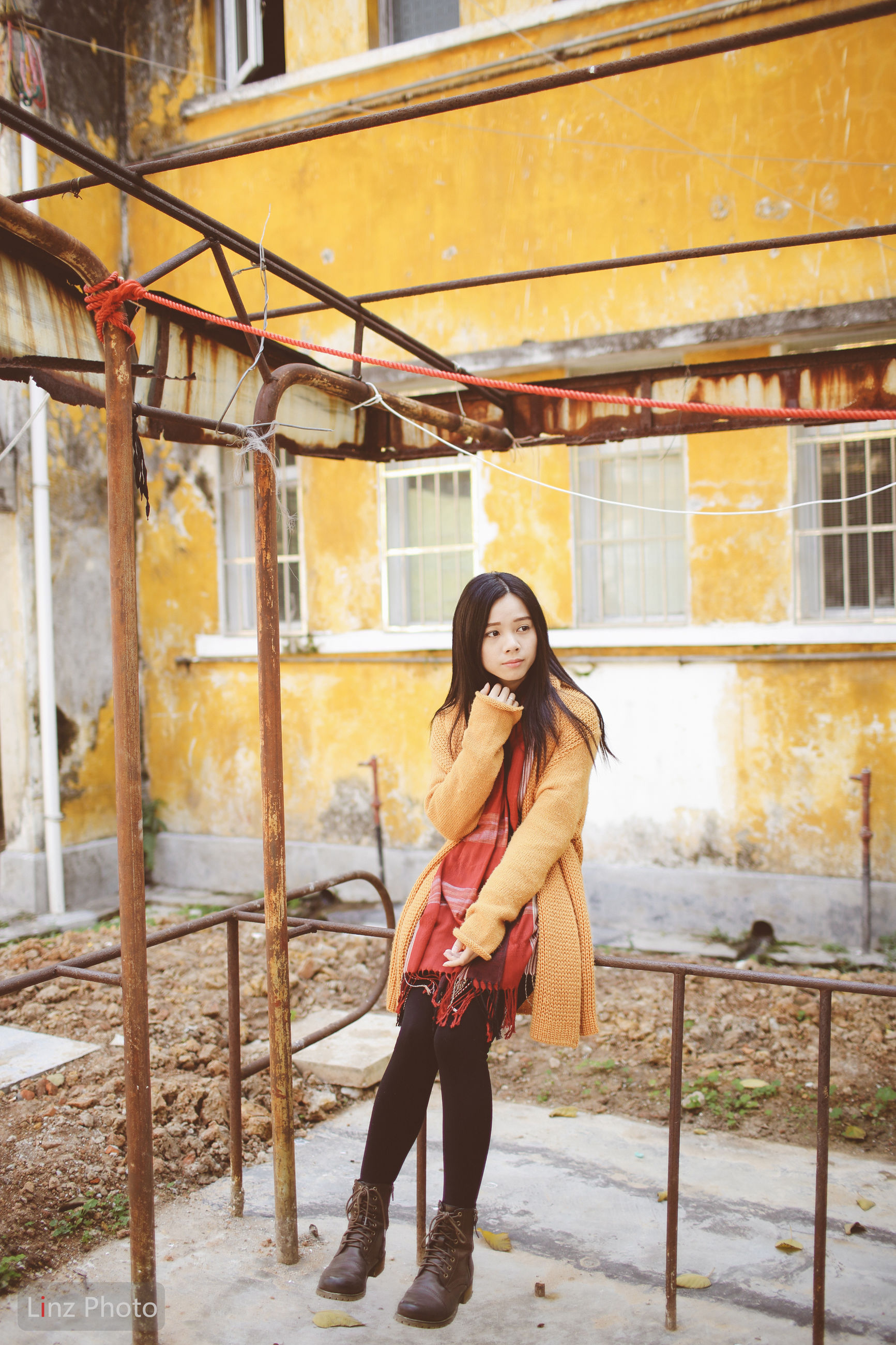 lifestyles, building exterior, full length, young adult, leisure activity, casual clothing, architecture, built structure, person, standing, young women, warm clothing, long hair, three quarter length, front view, holding, graffiti, street